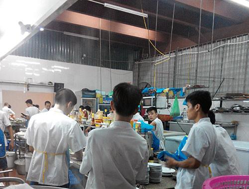 Khu vực bếp rộng lớn với nhiều đầu bếp đang tất bật chế biến